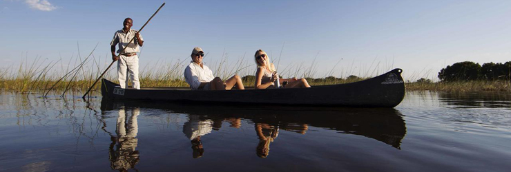 Mokoro (dug out canoes) glide silently over the clear Okavango waters